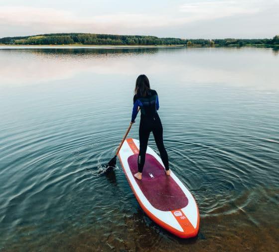 femme en combi sur paddle